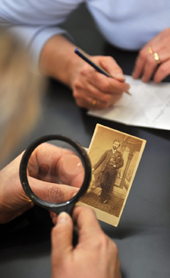 Family researcher looking at a photograph with a magnifying glass