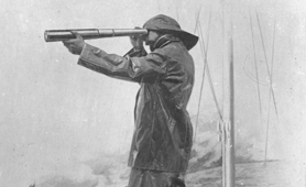 Illustration of member of the Coastguard looking through a telescope, 1907 (Catalogue reference: COPY 1/511/276)